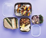 Salads, vegetable kebabs and sandwiches in lunch boxes