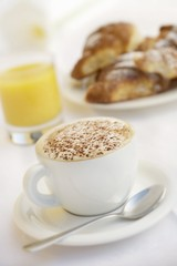 A cup of cappuccino, orange juice and brioches