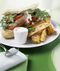 Steak sandwich with rocket, tomatoes and potato wedges