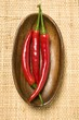 Three chili peppers in wooden bowl