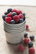 Raspberries and blueberries in metal container