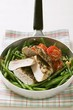 Chicken breast with green beans and tomatoes in frying pan