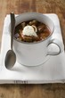 Goulash soup with sour cream in cup, with spoon