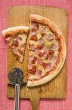 Ham pizza on chopping board (half and a slice)