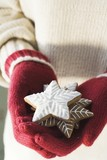 Hands in woollen gloves holding gingerbread stars