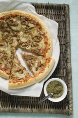Tuna and onion pizza, partly sliced, oregano beside it