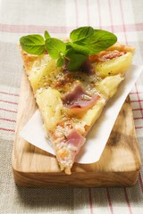 Slice of Hawaiian pizza with fresh oregano on chopping board