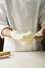 Shaping pizza dough by hand (stretching)