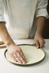 Pressing pizza dough into baking tin
