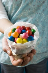 Hands holding coloured bubble gum balls in paper bag