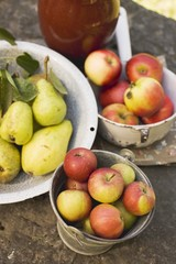 Fresh pears and apples in containers on stone wall