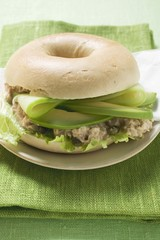 Bagel filled with avocado, tuna salad and capers