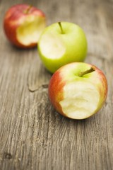 Three apples with bites taken on wooden background