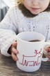 Small girl drinking large mug of cocoa