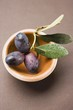 Olive sprig with black olives in terracotta bowl (overhead)