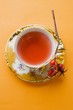 Rose hip tea in china cup, fresh rose hips on cup