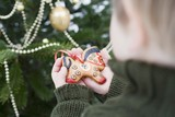 Child holding gingerbread horse (tree ornament)