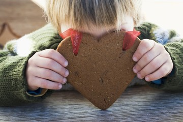 Small boy holding gingerbread heart in front of his face