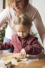 Mother and child cutting out Christmas biscuits