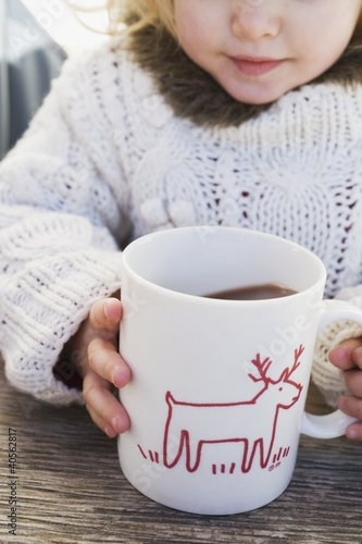 Small girl drinking large mug of cocoa