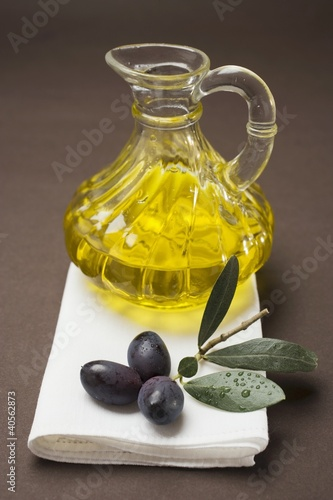 Olive sprig with black olives, carafe of olive oil behind