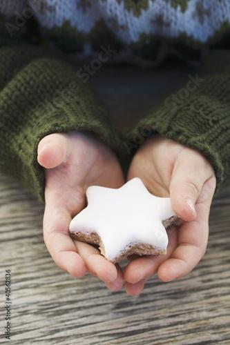 Child's hands holding cinnamon star