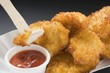 Chicken nuggets with ketchup in paper dish