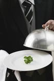 Butler serving fresh parsley on plate with dome cover