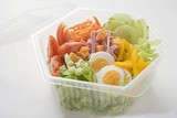 Iceberg lettuce, ham, cheese, egg & vegetables in plastic bowl