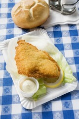 Fish fillet with mayonnaise and bread roll in snack bar