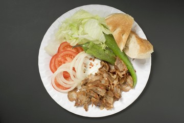 Döner meat with vegetables and flatbread on paper plate