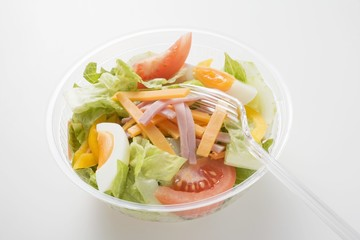 Iceberg lettuce, ham, cheese, egg & tomatoes in plastic bowl