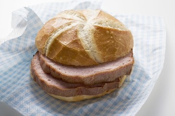 Slices of Leberkäse (type of meatloaf) in a roll on paper napkin