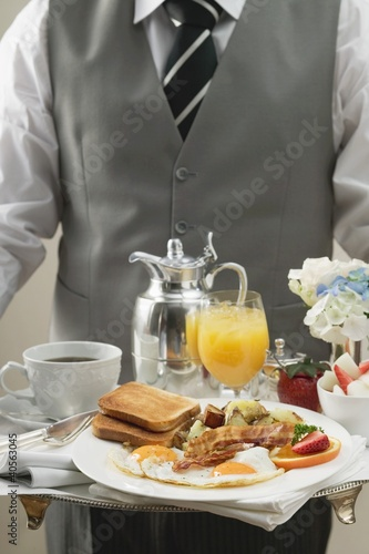 Butler serving breakfast tray with bacon, eggs & toast