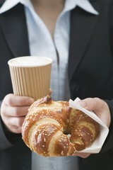 Woman holding pretzel-style croissant & coffee in plastic cup