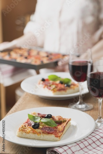Slices of pepperoni pizza with olives, glasses of red wine