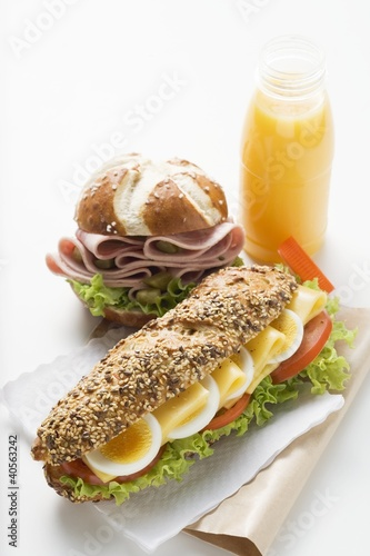 Egg in granary roll, sausage in pretzel roll, orange juice