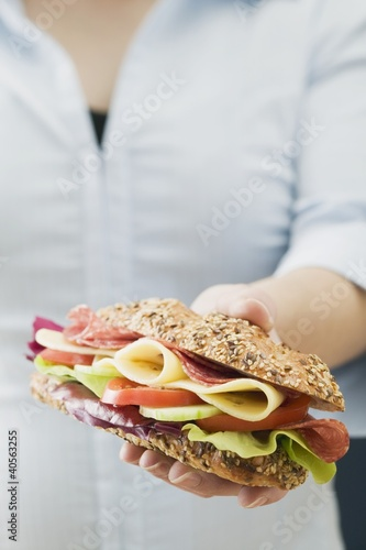 Woman holding granary roll filled with sausage, cheese & salad