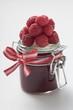 Jar of raspberry jam, fresh raspberries on top of jar