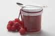 Jar of raspberry jam with spoon, fresh raspberries beside it