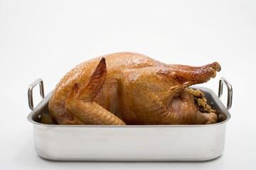 Stuffed roast turkey in roasting tin