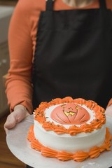 Woman holding Halloween cake on plate