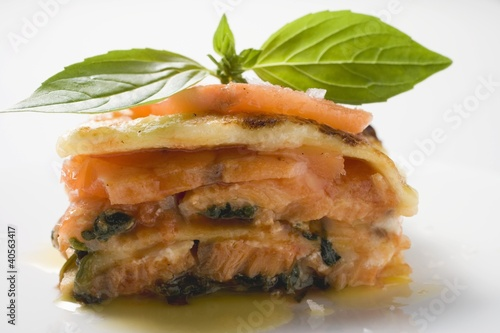 Portion of salmon lasagne with basil