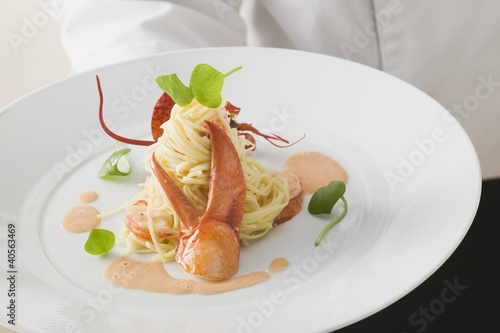 Waiter serving linguine with lobster