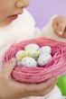 Child holding Easter eggs in pink nest