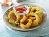 Battered deep-fried onion rings with ketchup