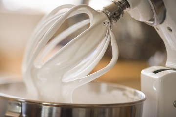 Whipped cream on balloon whisk of food mixer