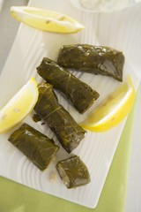 Stuffed vine leaves with lemon wedges