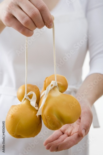 Woman holding two Provolone cheeses