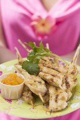 Woman holding plate of satay and chutney